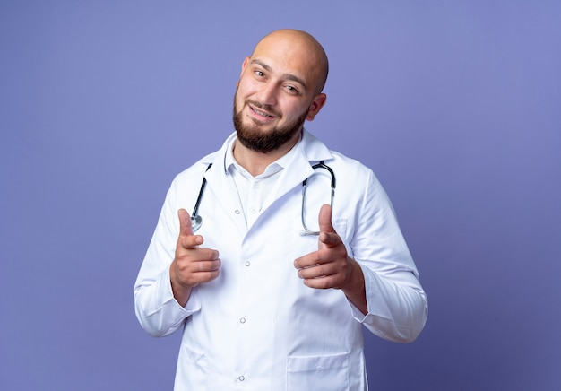 Pleased young bald male doctor wearing medical robe and stethoscope showing you gesture isolated on blue background