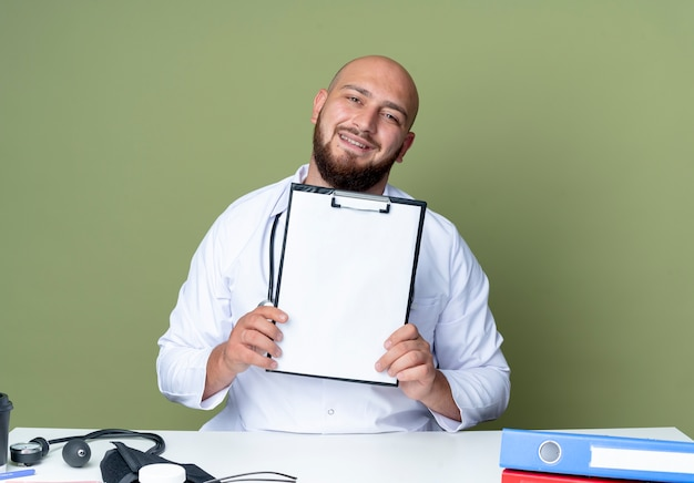Pleased young bald male doctor wearing medical robe and stethoscope sitting at desk work with medical tools holding clipboard isolated on green background