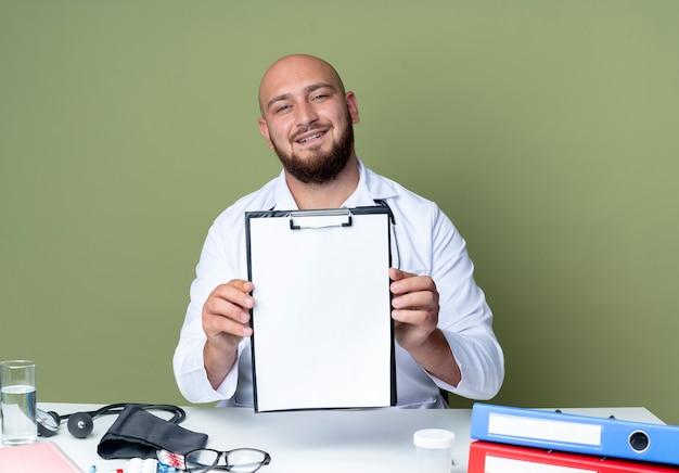 Lieta giovane maschio calvo medico indossando accappatoio medico e uno stetoscopio seduto alla scrivania lavora con strumenti medici tenendo appunti isolati su sfondo verde