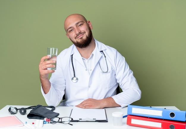 Lieta giovane maschio calvo medico indossando abito medico e uno stetoscopio seduto alla scrivania lavora con strumenti medici tenendo un bicchiere di acqua isolato su sfondo verde