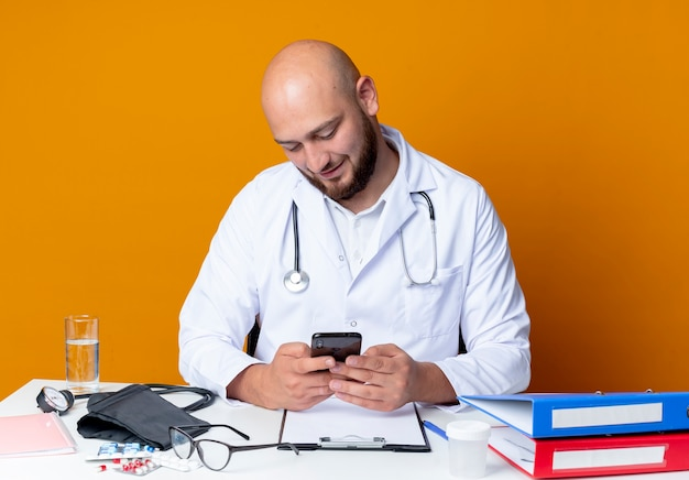 Pleased young bald male doctor wearing medical robe and stethoscope sitting at work desk with medical tools dial number isolated on orange background