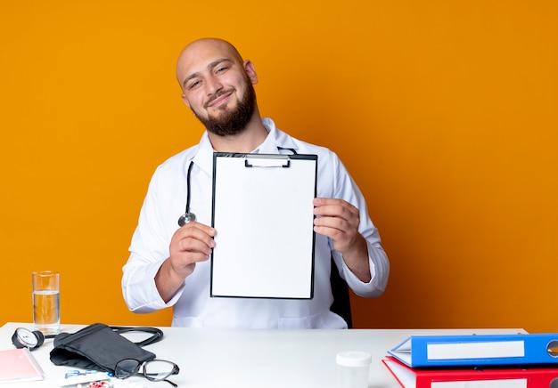 Lieta giovane maschio calvo medico indossando abito medico e uno stetoscopio seduto alla scrivania con strumenti medici tenendo appunti isolato su sfondo arancione