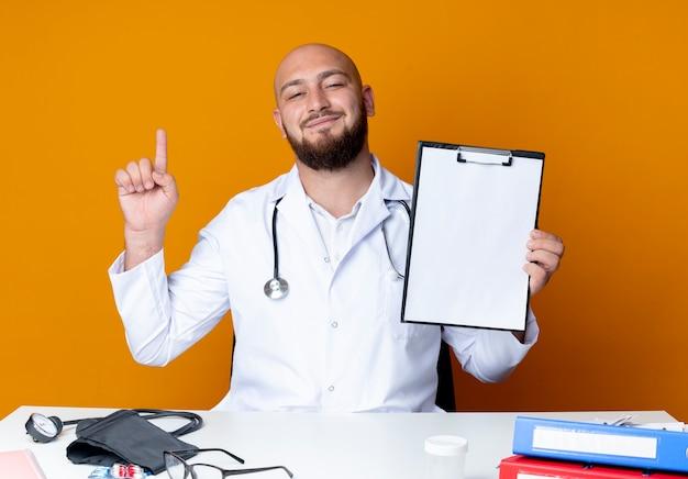 Lieto giovane maschio calvo medico indossando abito medico e stetoscopio seduto alla scrivania con strumenti medici tenendo appunti e punti in alto isolato su sfondo arancione