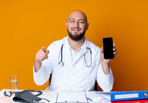 Pleased young bald male doctor wearing medical robe and stethoscope sitting at work desk with medical tools holding phone and showing you gesture isolated on orange background