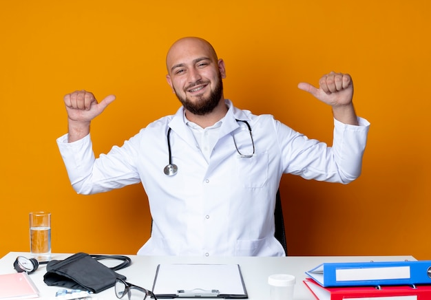 Pleased young bald male doctor wearing medical robe and stethoscope sitting at work desk with medical tools points at himself isolated on orange background