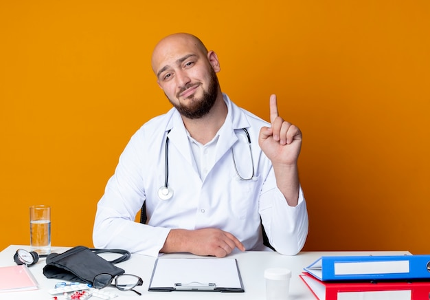 Pleased young bald male doctor wearing medical robe and stethoscope sitting at work desk with medical tools points at up isolated on orange background