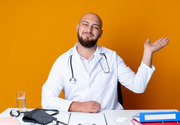 Lieto giovane maschio calvo medico indossando abito medico e stetoscopio seduto alla scrivania con punti di strumenti medici con la mano a lato isolato su sfondo arancione