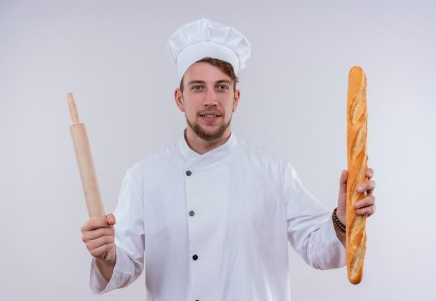 Un felice giovane chef barbuto uomo che indossa l'uniforme bianca del fornello e cappello che tiene il pane baguette con il mattarello mentre guarda su un muro bianco