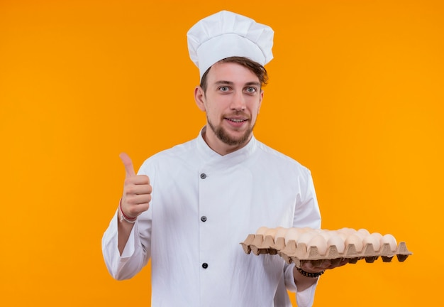 A pleased young bearded chef man wearing white cooker uniform and hat holding a carton of eggs while looking on an orange wall