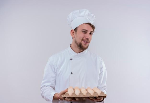 Un felice giovane chef barbuto uomo che indossa l'uniforme bianca del fornello e il cappello che tiene un cartone di uova mentre guarda su una parete bianca