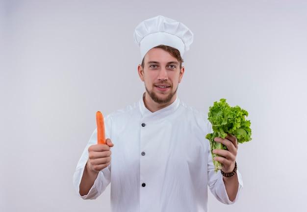Un felice giovane chef barbuto uomo bianco che indossa un fornello uniforme e cappello azienda foglia verde lattuga con carota mentre guarda su un muro bianco