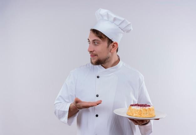 Un felice giovane chef barbuto uomo che indossa l'uniforme bianca del fornello e il cappello che tiene un piatto con la torta mentre guarda il lato su un muro bianco