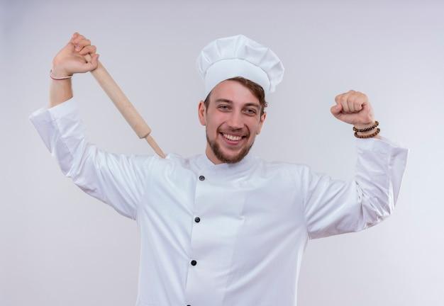 Un felice giovane chef barbuto uomo bianco che indossa un fornello uniforme e cappello tenendo il mattarello con il pugno chiuso mentre guarda su un muro bianco