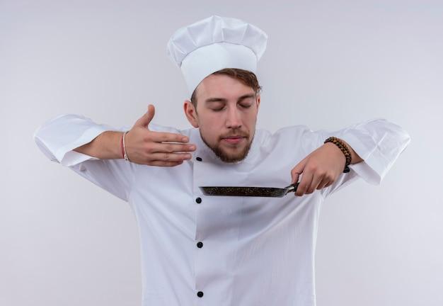 Un felice giovane uomo barbuto chef indossando l'uniforme bianca fornello e cappello odorando padella su una parete bianca