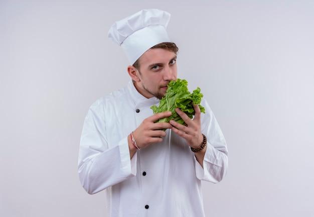 Un felice giovane chef barbuto uomo che indossa l'uniforme bianca del fornello e cappello odorante di lattuga a foglia verde mentre guarda un muro bianco