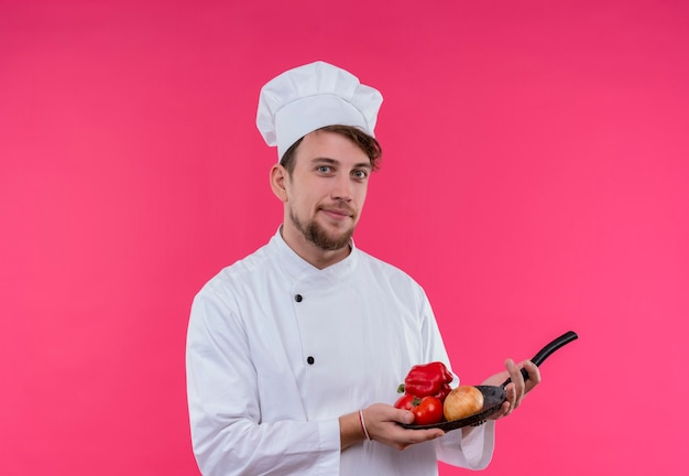 A pleased young bearded chef man in white uniform holding frying pan with fresh vegetables such as onion,tomato and bell pepper while looking on a pink wall