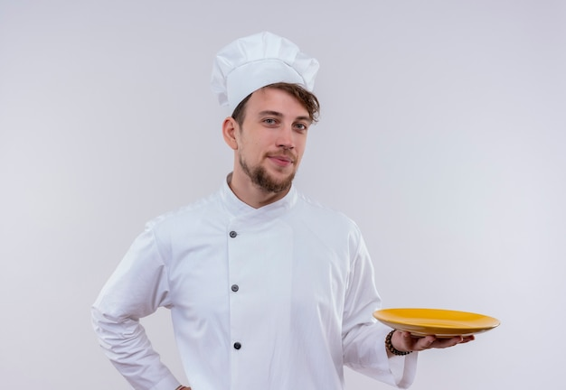 A pleased young bearded chef man in white uniform presenting a yellow plate ready for food while looking on a white wall