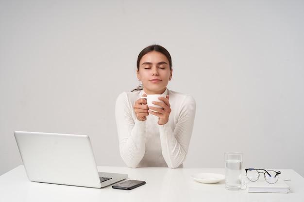 コーヒーブレイクを持ち、白いセラミックカップを保ち、目を閉じて、白い壁の上に座って心地よく笑っているポニーテールの髪型を持つ若い美しいブルネットの女性を喜ばせます
