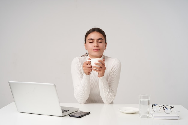 Pleased young beautiful brunette woman with ponytail hairstyle having coffee break and keeping white ceramic cup and smiling pleasantly with closed eyes, sitting over white wall