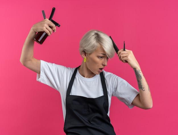 Довольная молодая красивая женщина-парикмахер в униформе держит парикмахерские инструменты, расчесывая волосы, изолированные на розовой стене