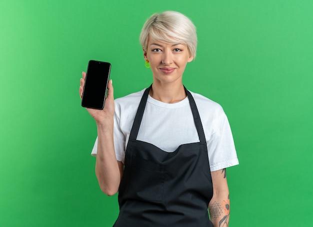 Довольная молодая красивая женщина-парикмахер в униформе, держащая телефон, изолированную на зеленой стене