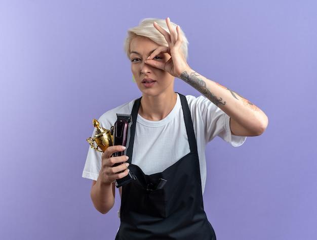 Довольная молодая красивая женщина-парикмахер в униформе держит кубок победителя с машинками для стрижки волос, показывая жест взгляда, изолированный на синей стене