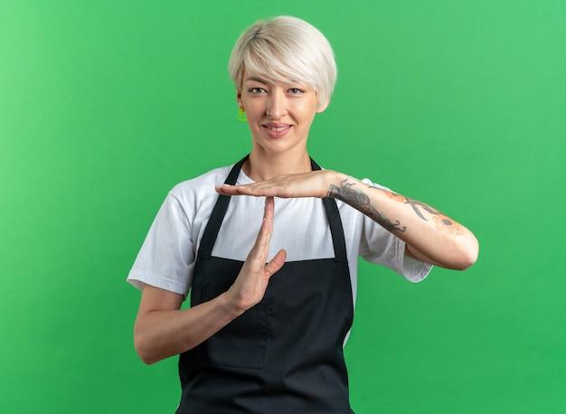 緑の壁に分離されたタイムアウトジェスチャーを示す制服を着た若い美しい女性の理髪師を喜ばせる