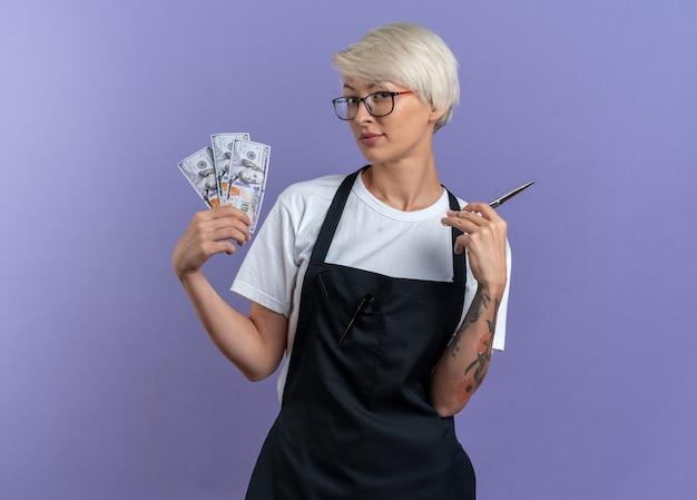 파란색 벽에 고립 된 가위로 현금을 들고 안경을 착용하는 제복을 입은 기쁘게 젊은 아름다운 여성 이발사