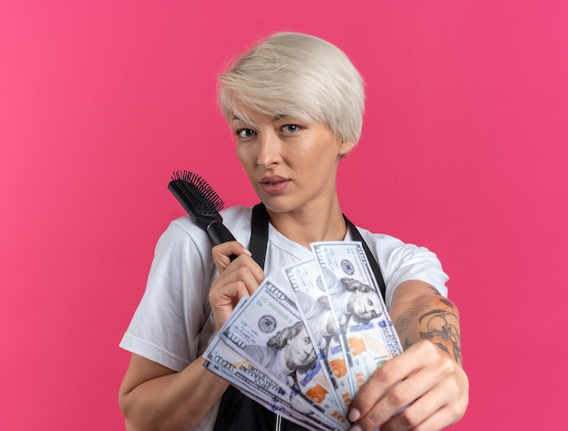 Pleased young beautiful female barber in uniform holding out comb with cash  isolated on pink wall