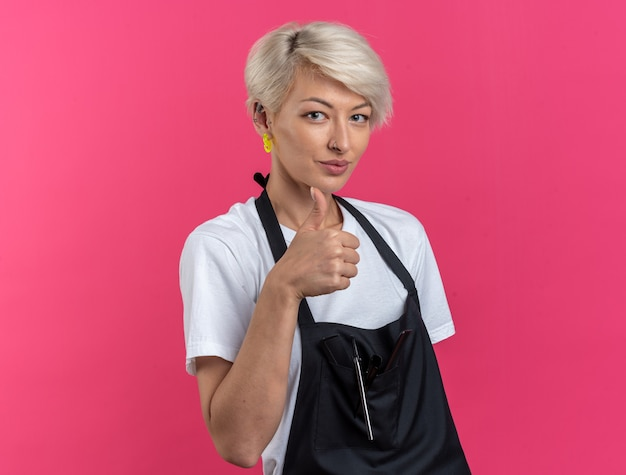 Pleased young beautiful female barber in uniform showing thumb up isolated on pink wall
