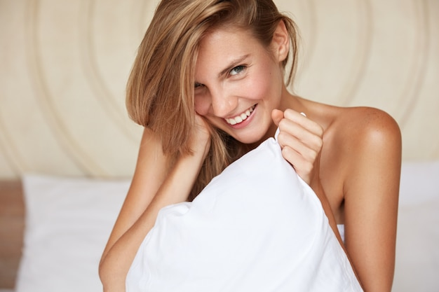 Pleased young beautiful female model with happy expression and naked body, poses on comfortable bed in modern apartment, smiles happily as enjoys great morning and starting new day. bed time concept