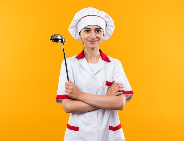 Pleased young beautiful girl in chef uniform holding ladle crossing hands isolated on orange wall