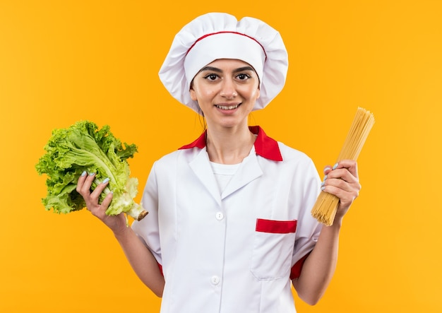 Pleased young beautiful girl in chef uniform holding salad with spaghetti
