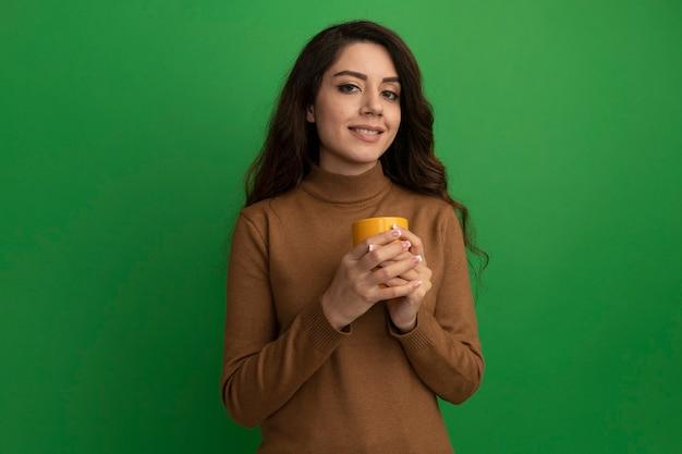 Довольная молодая красивая девушка держит чашку чая, изолированную на зеленой стене с копией пространства