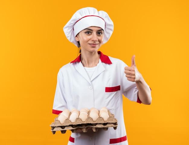 オレンジ色の壁に分離された親指を示す卵のバッチを保持しているシェフの制服を着た若い美しい少女を喜ばせる