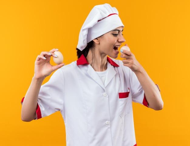 卵を保持し、オレンジ色の壁に分離して試してシェフの制服を着た若い美しい少女を喜ばせる