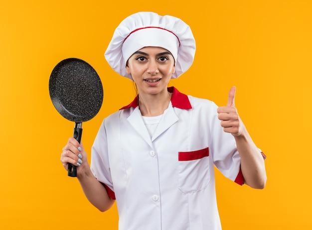 Довольная молодая красивая девушка в униформе шеф-повара держит сковороду, показывая большой палец вверх изолированной на оранжевой стене