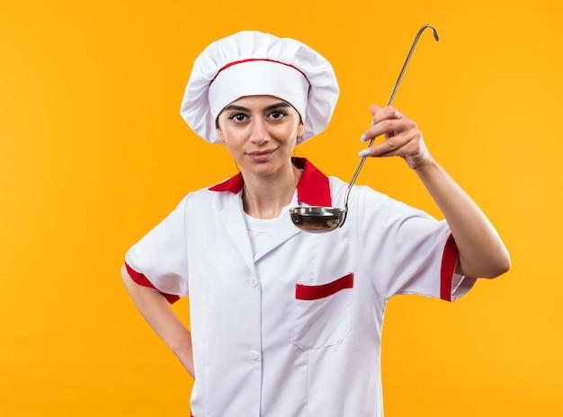 Довольная молодая красивая девушка в униформе шеф-повара, держащая ковш, кладет руку на бедро, изолированную на оранжевой стене