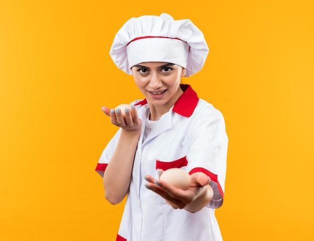 Довольная молодая красивая девушка в униформе шеф-повара, протягивая яйца перед камерой