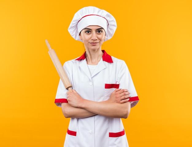 Довольная молодая красивая девушка в униформе шеф-повара держит скалку за руки