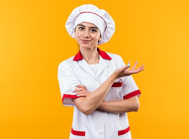 Довольная молодая красивая девушка в очках униформы шеф-повара с рукой сбоку, изолированной на оранжевой стене