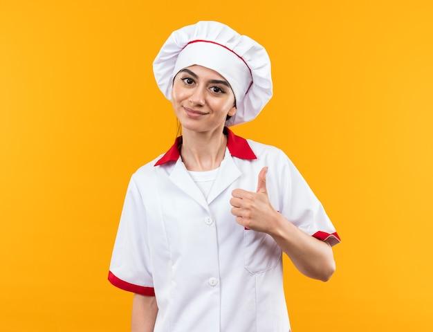 オレンジ色の壁に分離された親指を見せてシェフの制服を着た若い美しい少女を喜ばせる