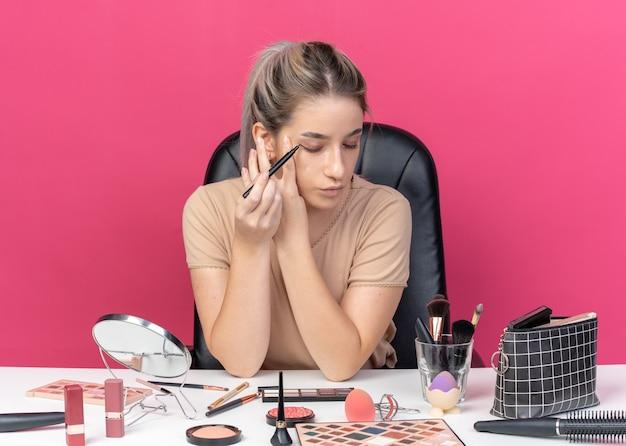 기쁘게 젊은 아름 다운 소녀 메이크업 도구와 테이블에 앉아 아이 라이너 핑크 벽에 고립 된 화살표를 그립니다