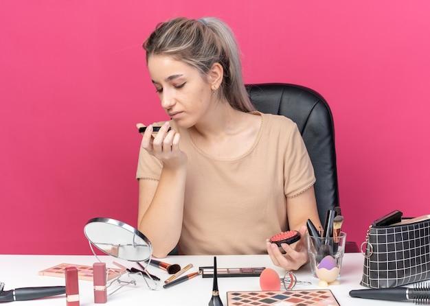 Довольная молодая красивая девушка сидит за столом с инструментами для макияжа и нюхает порошковые румяна, изолированные на розовой стене