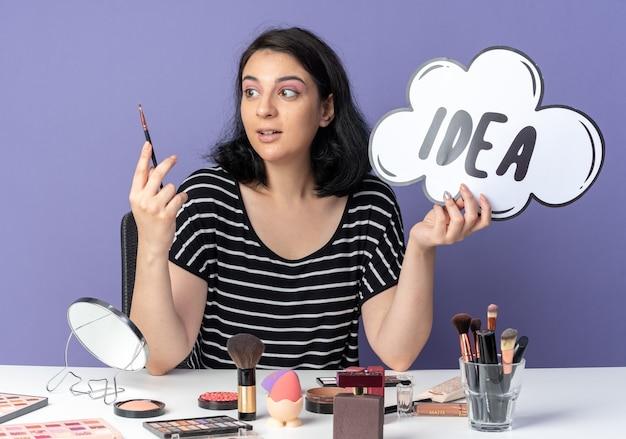 Довольная молодая красивая девушка сидит за столом с инструментами для макияжа, держа пузырь идеи с кистью для макияжа, изолированной на синей стене