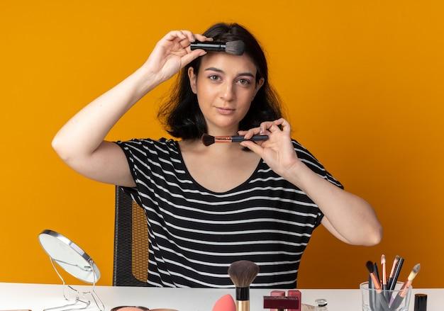 満足している若い美しい少女は、オレンジ色の壁で隔離された額とあごに化粧ブラシを保持している化粧ツールでテーブルに座っています