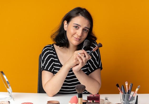 喜んで若い美しい少女は、オレンジ色の壁に分離されたパウダーブラシを保持している化粧ツールでテーブルに座っています。
