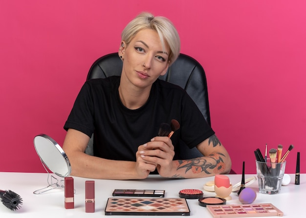 ピンクの壁に分離されたパウダーブラシを保持している化粧ツールでテーブルに座って喜んで若い美しい少女