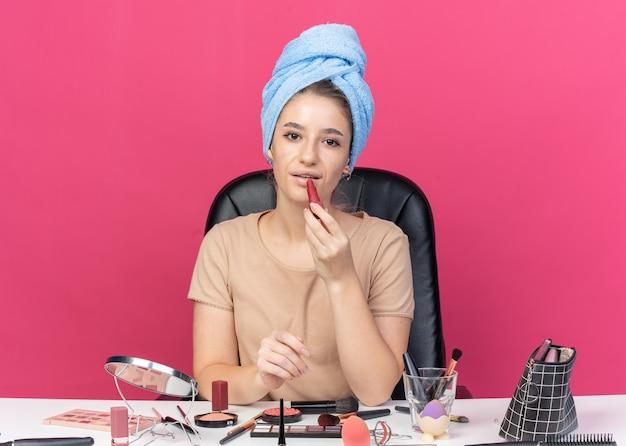 Довольная молодая красивая девушка сидит за столом с инструментами для макияжа, завернув волосы в полотенце, наносит помаду, изолированную на розовой стене