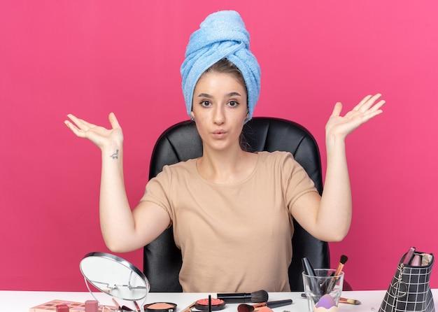 Довольная молодая красивая девушка сидит за столом с инструментами для макияжа, обернув волосы полотенцем, поднимая руки, изолированные на розовой стене